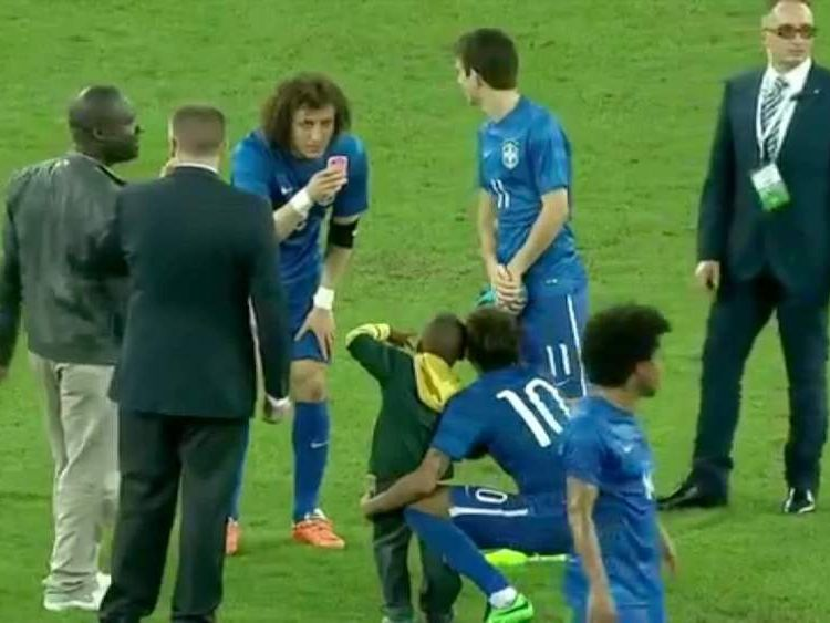 Chelsea defender David Luiz takes a picture of the Neymar with the little boy