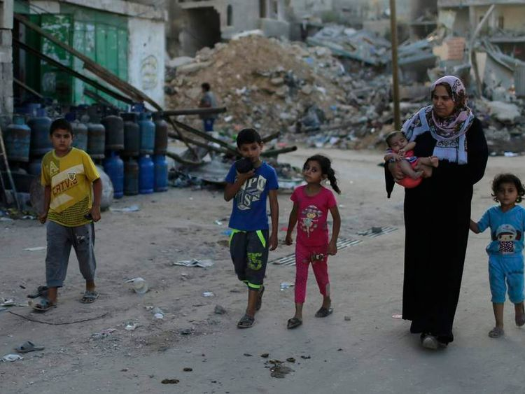 Palestinians flee their house on foot in Beit Hanoun town in the northern Gaza Strip