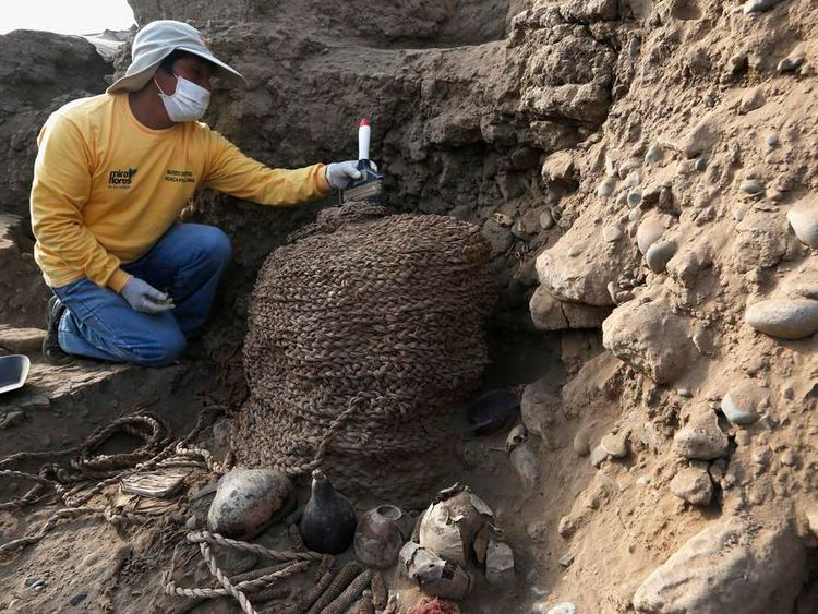 An archaeologist cleans a recently discovered tomb of an intact mummy of the Wari prehispanic culture in Lima's Huaca Pucllana ceremonial complex, at Miraflores
