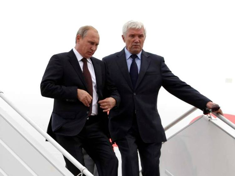 Russian President Vladimir Putin, accompanied by Russian Ambassador to Belarus Alexander Surikov, walks down the stairs upon his arrival at an airport outside Minsk