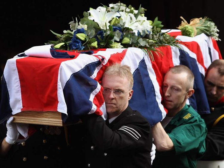 Emergency service workers carry the coffin of PC David Rathband