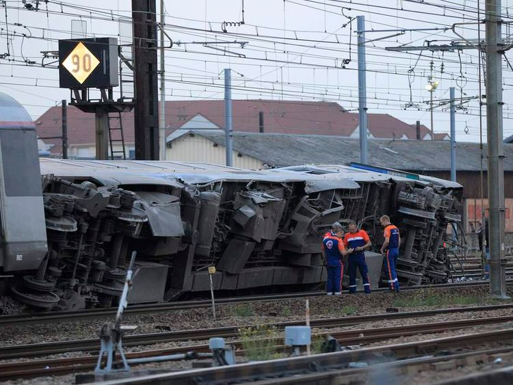 Rescue workers stand next to the wreckage of a derailed intercity train at the Bretigny-sur-Orge station near Paris