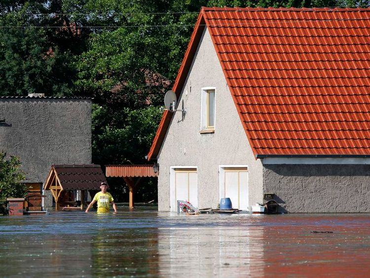 A resident wades in front of his house after the river Elbe flooded the village of Kabelitz