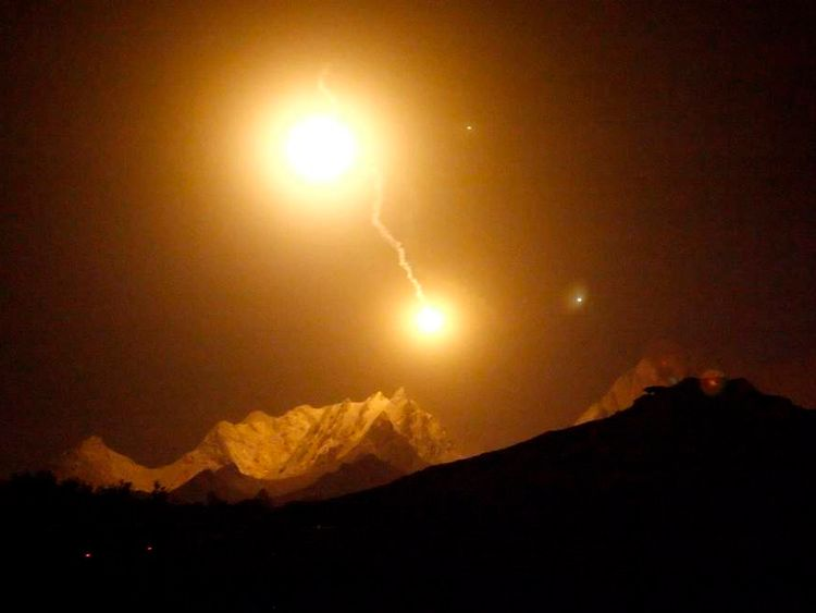 Illumination rounds fired by the NATO-led coalition light up mountains above the village of Panjwaii in Kandahar province, southern Afghanistan