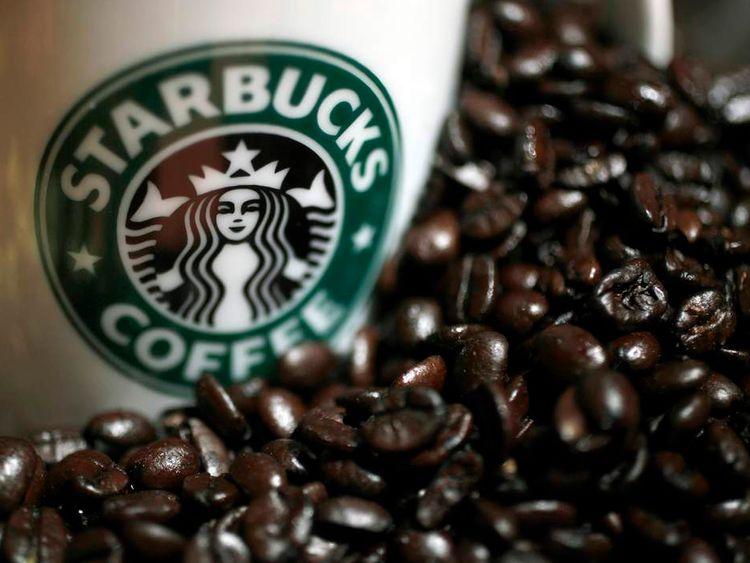 A Starbucks mug next to coffee beans