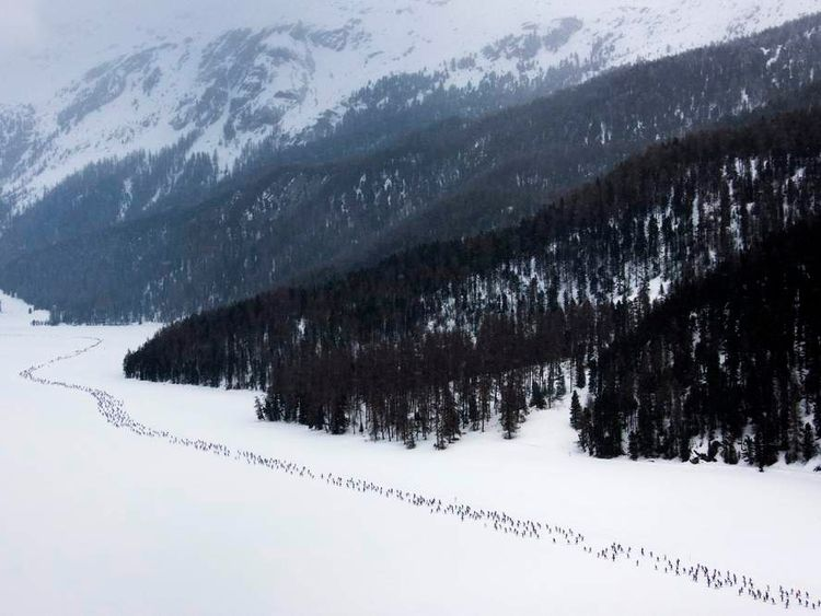 Cross country skiers race over the frozen lake Sils during the Engadin Ski Marathon near Sils