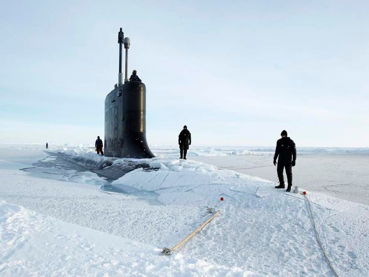 U.S. Navy safety swimmers stand on the deck of the Virginia class submarine USS New Hampshire after it surfaced in the Arctic Ocean north of Prudhoe Bay