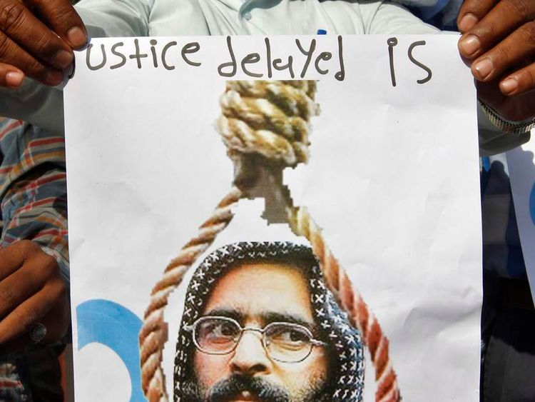 A member of a social group holds a placard with a picture of Afzal Guru before burning it during a protest in Ahmedabad