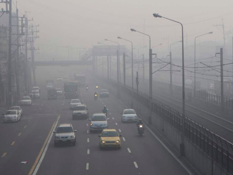 Motorists switch on their headlights while crossing a highway covered by smog in Manila