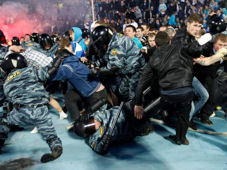 Policemen chase a supporter of Zenit St. Petersburg as he celebrates his team's victory against Dinamo Moscow in St.Petersburg