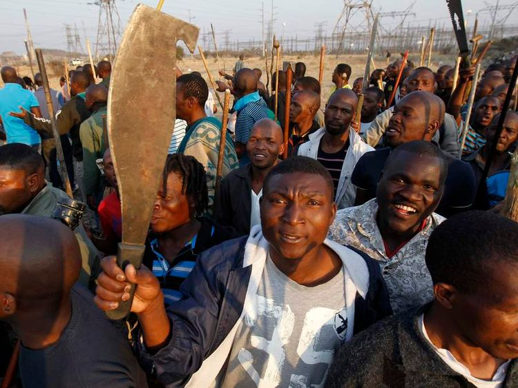 Crowd of miners wave machetes