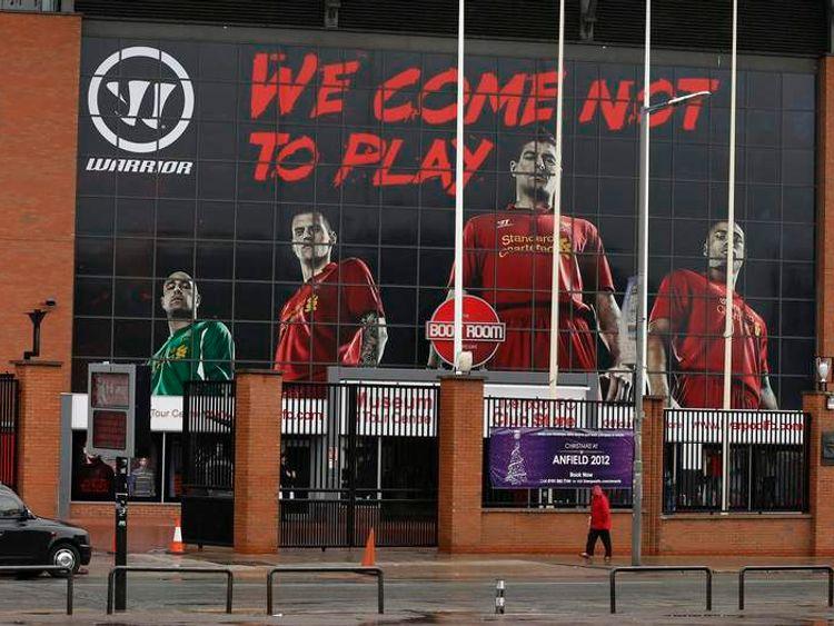 A woman walks past Liverpool Football Club's Anfield stadium in Liverpool