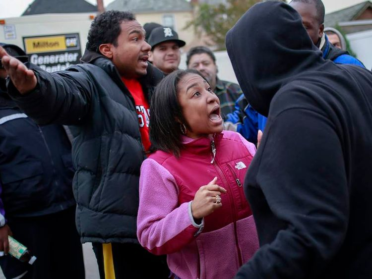 Local residents argue for their place in line while waiting to get fuel at a gas station