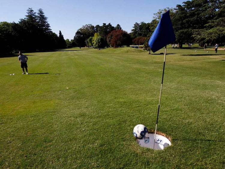 A man kicks the ball into the hole as he competes in a FootGolf tournament on the outskirts of Buenos Aires.