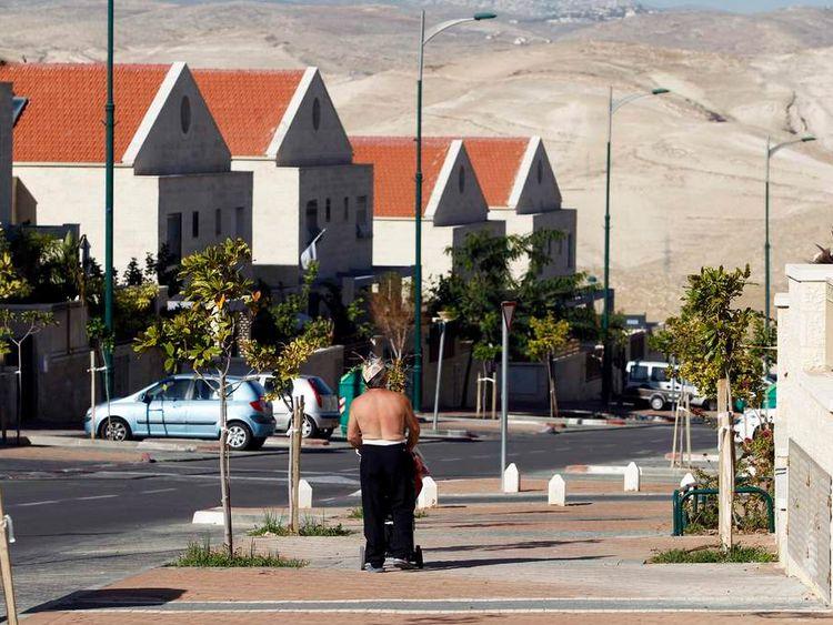 Israeli man walks on a pavement in a West Bank Jewish settlement near Jerusalem