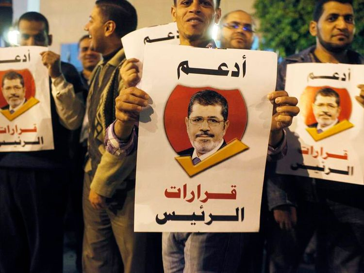 """Pro-Morsi supporters hold banners reading """"I support the President's decisions"""", during a march in Cairo"""