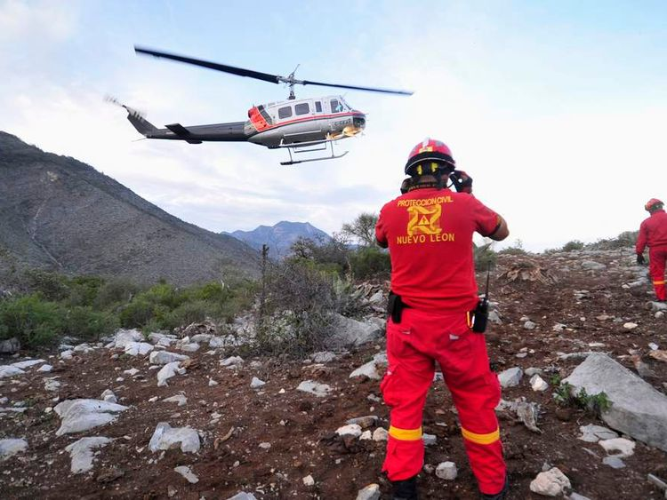 Emergency workers at the crash site of a plane with Mexican-American singer Jenni Rivera on board