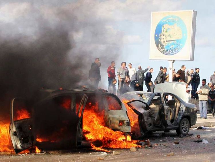 An anti-Morsi protesters shout slogans in front of burning cars during clashes with Morsi supporters in Alexandria
