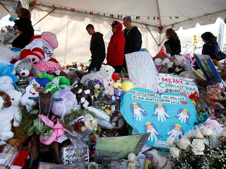 People pay their respects at a makeshift memorial in Newtown