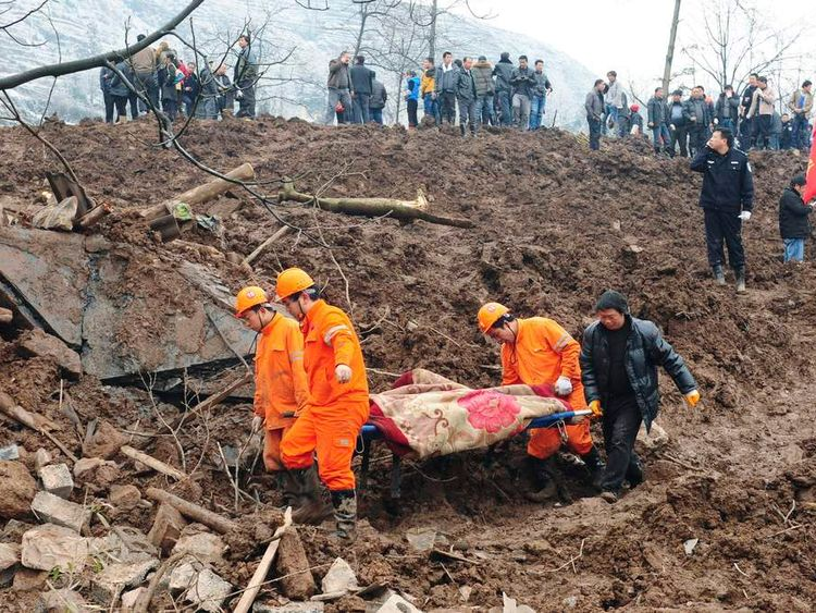 Rescuers carry the body of a victim after a landslide hit Zhenxiong county, Yunnan province