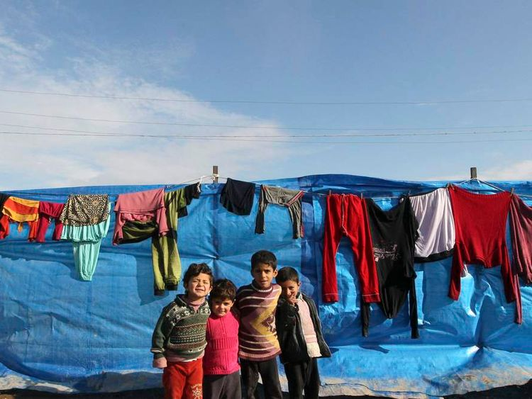 Young Syrian refugees stand in front of a tent at Bab al-Salam refugee camp in Azaz