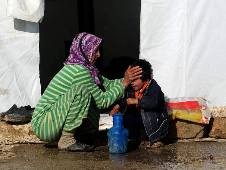 A Syrian refugee cleans a boy's face outside a tent at Bab al-Salam refugee camp in Azaz