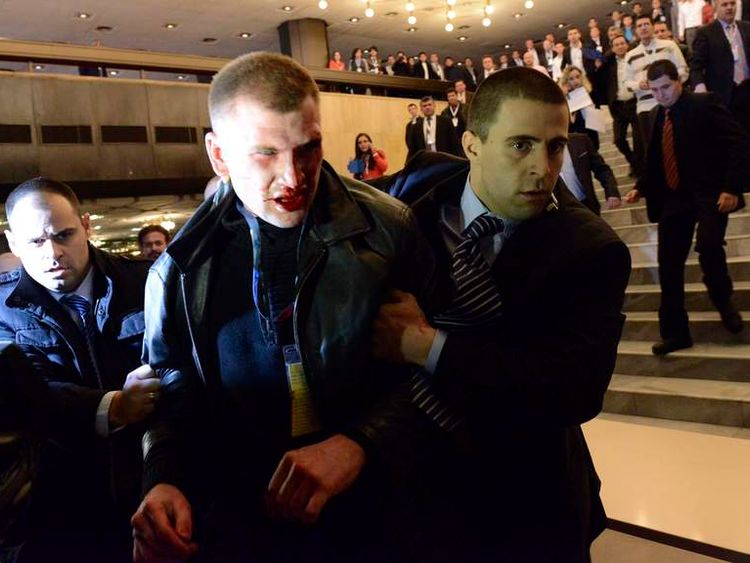 An unidentified man is escorted by security personnel after attacking Ahmed Dogan, leader of Bulgaria's Movement for Rights and Freedom (MRF) party, in Sofia