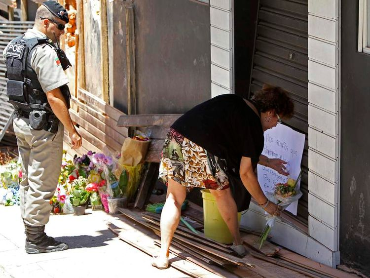 A policeman watches as Maria Schiller Muller places flowers and a poster in front of Boate Kiss nightclub in the southern city of Santa Maria