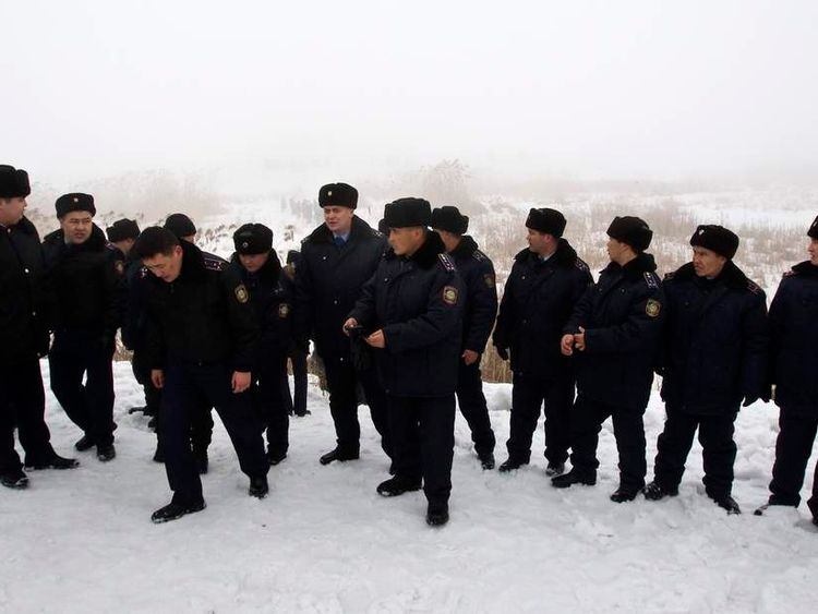 Interior Ministry members block the way near the site of the plane crash outside Almaty