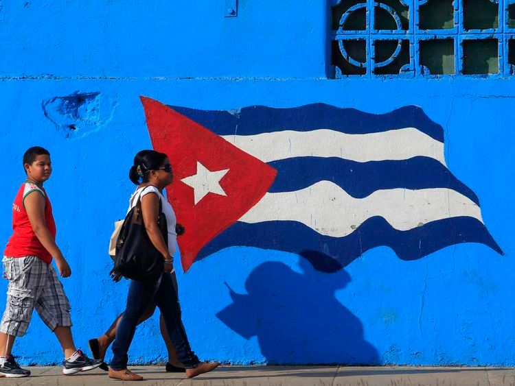 People walk beside a Cuban flag painted on a wall in Matanzas in central Cuba
