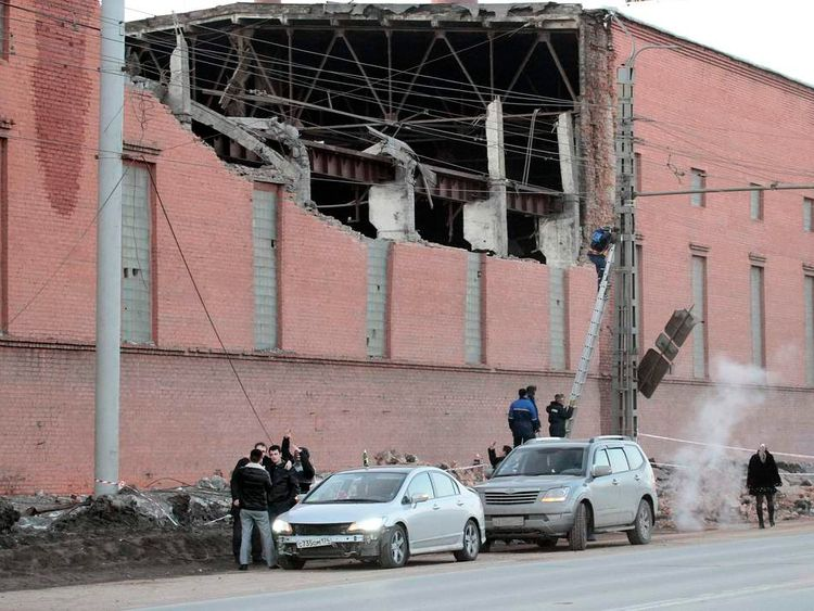 Workers examine damage on buildings in Chelyabinsk