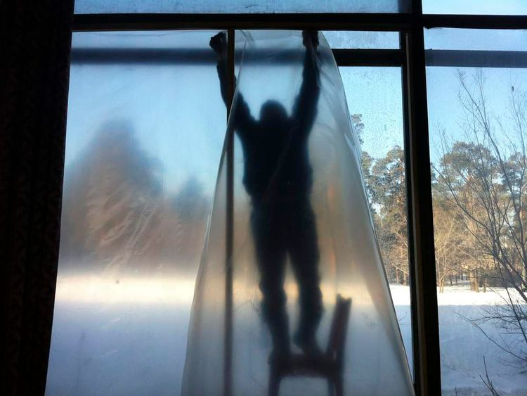 A man repairs the window of a sports hall damaged by a shockwave from a meteor in the Urals city of Chelyabinsk