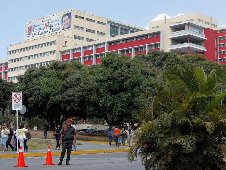 People walk at the entrance of the military hospital, where President Chavez is being treated, in Caracas