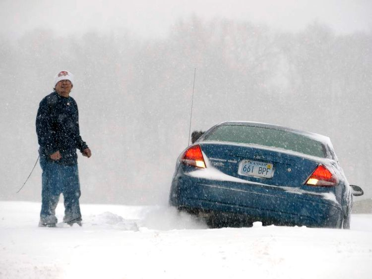 A man stands next to his car that is stuck in the snow during a blizzard in Kansas City