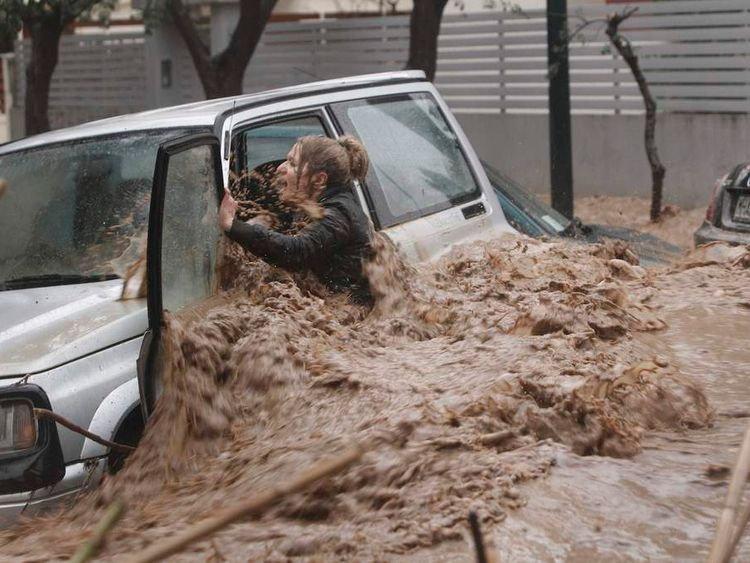 A woman stuck in her car reacts as flood waters gush past her during heavy rain in Chalandri suburb north of Athens