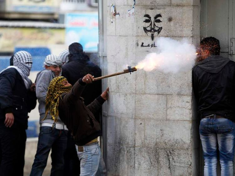 A Palestinian protester uses a makeshift launcher to shoot fire crackers during clashes with Israeli soldiers and border policemen in Hebron