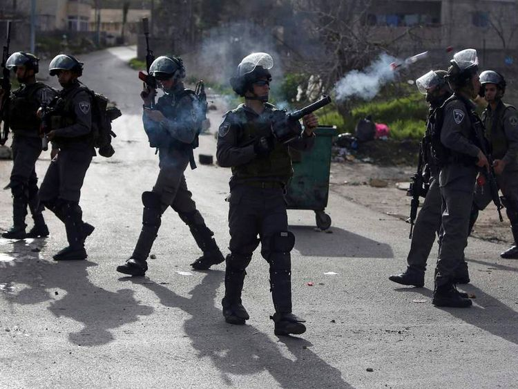 An Israeli border policeman fires a tear gas canister during clashes with stone-throwing Palestinian protesters near Ramallah