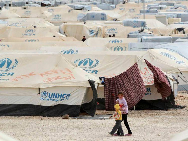 Syrian refugee children walk along tents at the Al Zaatri refugee camp in the Jordanian city of Mafraq