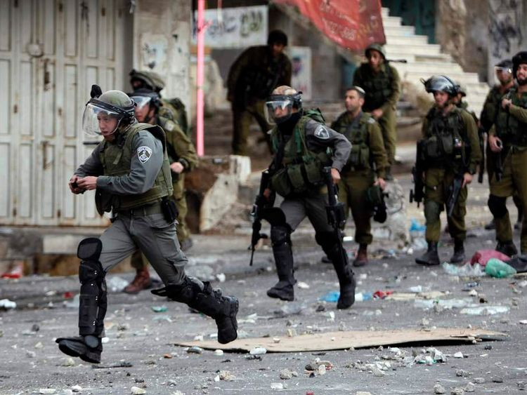 An Israeli border policeman holds a stun grenade as he runs during clashes with stone-throwing Palestinian protesters in Hebron
