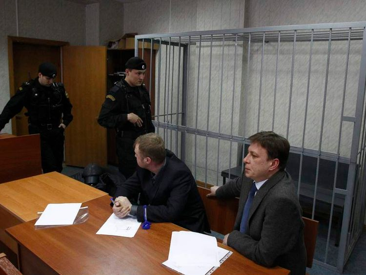 Attorneys of lawyer Sergei Magnitsky sit in front of an empty defendants' cage during a court session in Moscow