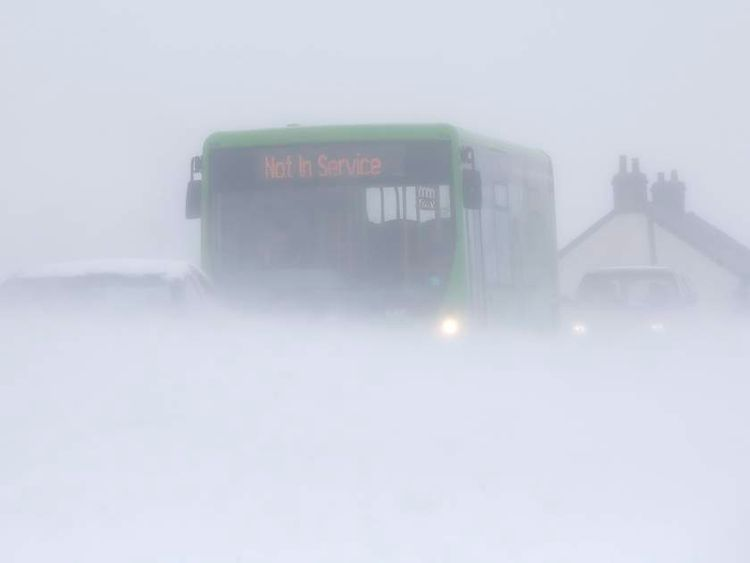 Motorists drive through snow blown from fields near Buxton in central England