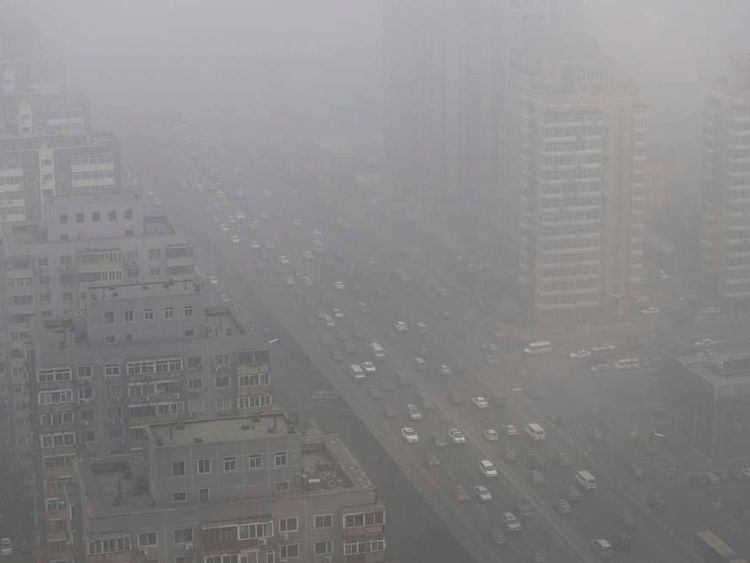 Cars drive on the Three Ring Road amid the heavy haze in Beijing