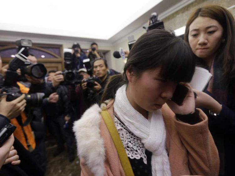 A relative of a passenger of Malaysia Airlines flight MH370 talks on a mobile phone as journalists attempt to interview her in Beijing
