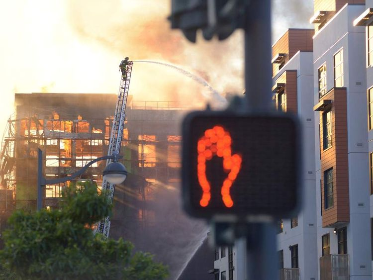 A firefighter battles flames at a construction site in the China Basin area of San Francisco