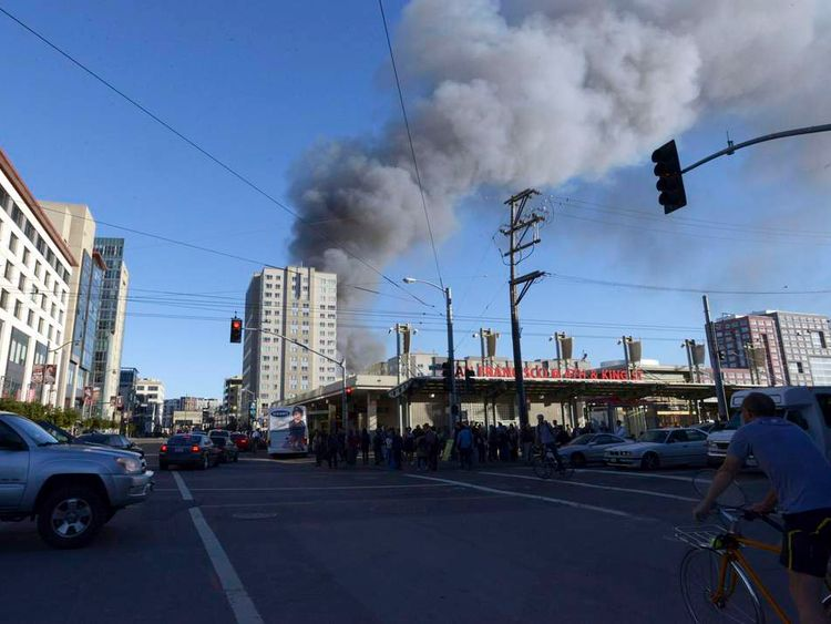 Traffic moves as smoke from a construction fire in the China Basin area of San Francisco rises above the city