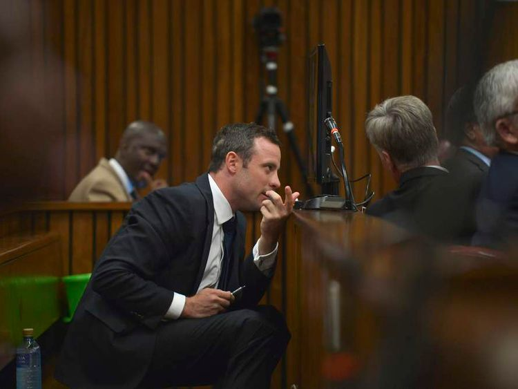 Oscar Pistorius confers with members of his legal team during court proceedings at the North Gauteng High Court in Pretoria