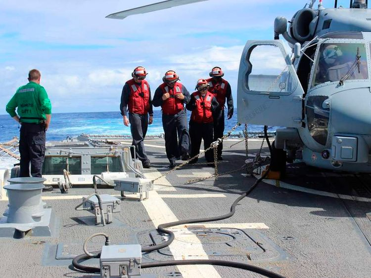 Sailors inspect the flight deck of the Arleigh Burke-class destroyer USS Kidd during search for missing Malaysian airliner
