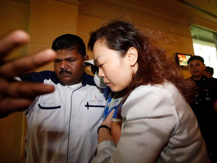 Chinese family members of a missing Malaysia Airlines MH370 passenger are escorted away from the media outside the media conference area at a hotel near Kuala Lumpur International Airport