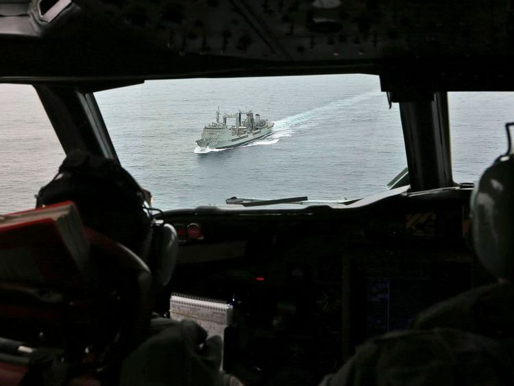 Flight Lieutenant Jason Nichols aboard a RAAF AP-3C Orion, looks ahead towards the Australian navy ship HMAS Success as they search for missing Malaysian Airlines flight MH370 over the southern Indian Ocean