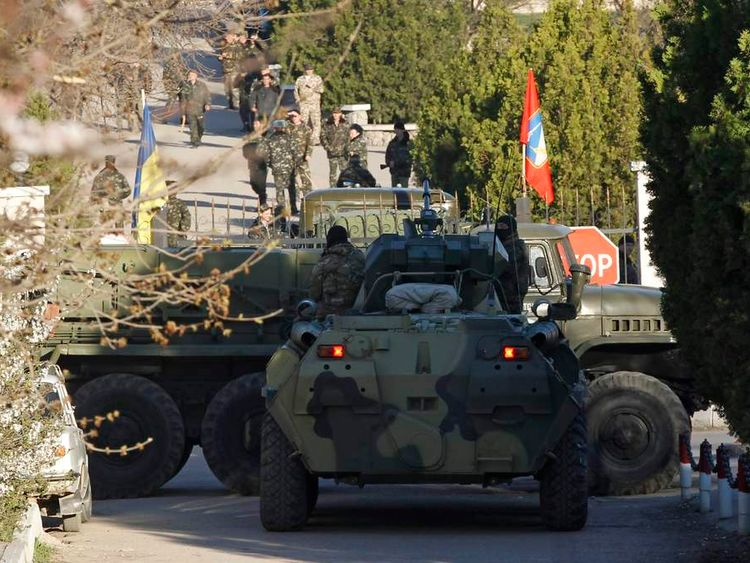 Military vehicles, believed to be Russian, are seen in front of the entrance to a military base, with Ukrainian servicemen seen in the background, in the Crimean town of Belbek